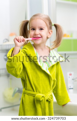 Smiling child kid little girl brushing teeth in bath - stock photo