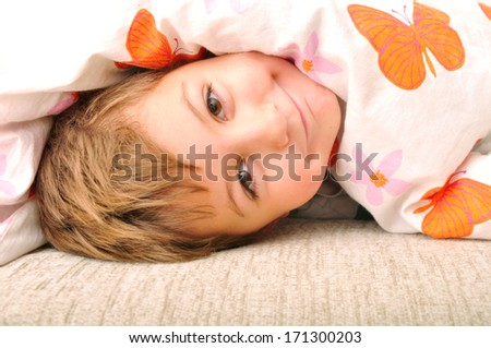 Smiling child lying in the bed under blanket - stock photo