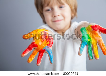 Smiling child showing his colored hands - stock photo