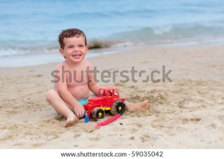 Smiling child sitting on the beach and playing with a car - stock photo