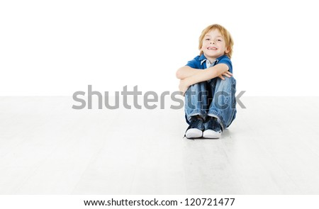 Smiling child sitting on white floor and looking at camera - stock photo