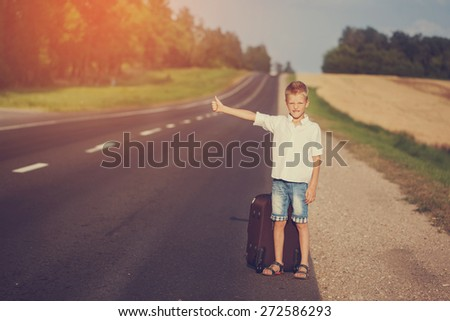 Smiling child with suitcase traveling hitchhiking. summer road. Toned image.                     - stock photo