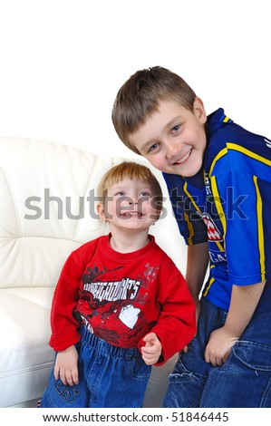 Smiling children, brother and sister, on white background and a sofa - stock photo