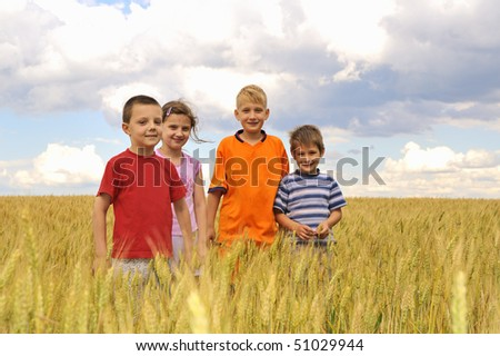 smiling children in cereal field - stock photo