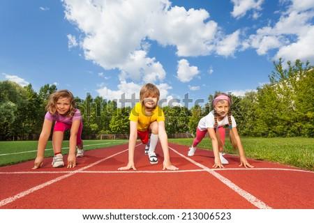 Smiling children on bending knees ready to run  - stock photo