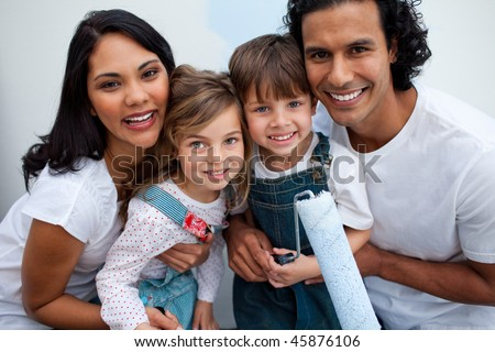 Smiling children painting a room with their parents in their new house - stock photo