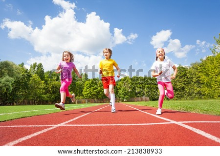 Smiling children running marathon together - stock photo