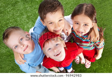 Smiling children spending time together at lawn and looking at cam - stock photo