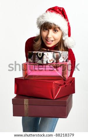Smiling christmas girl holding gifts wearing Santa hat. Isolated on white background. - stock photo
