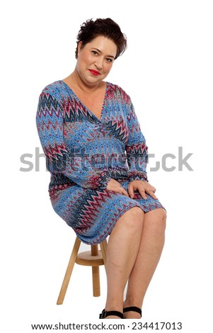 Smiling Chubby Middle Age Woman in Casual Dress, Sitting on Small Wooden Chair While Looking at the Camera. Isolated on White Background. - stock photo
