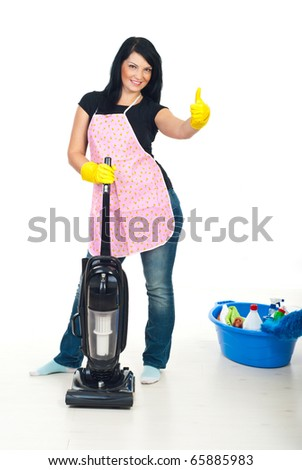 Smiling cleaning woman with pink apron holding a vacuum cleaner and giving thumb up - stock photo