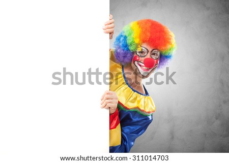 Smiling clown holding a blank panel - stock photo