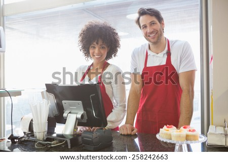 Smiling co-workers posing together behind the counter at the bakery - stock photo