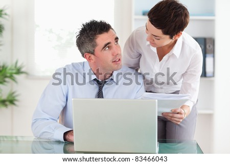 Smiling colleagues comparing a blueprint folder to an electronic one in an office - stock photo