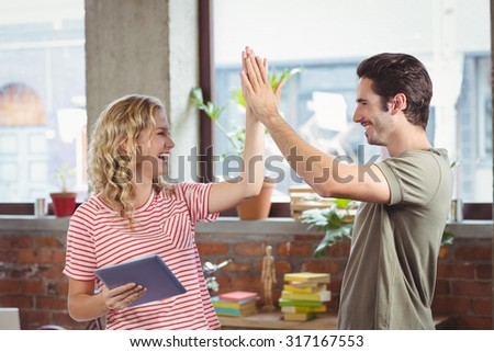 Smiling colleagues doing high five while working at creative office - stock photo