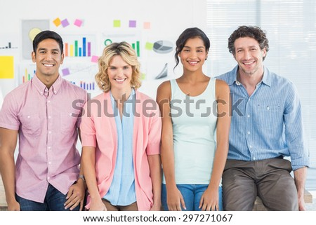 Smiling colleagues standing and posing in a line in the office - stock photo