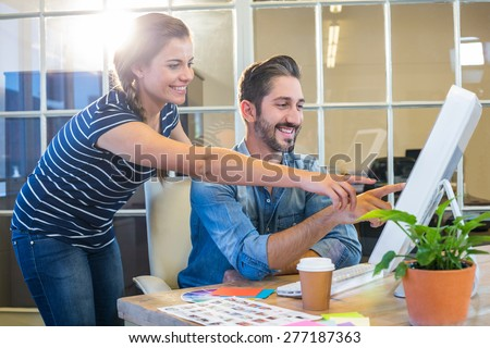 Smiling colleagues working together on computer in the office - stock photo
