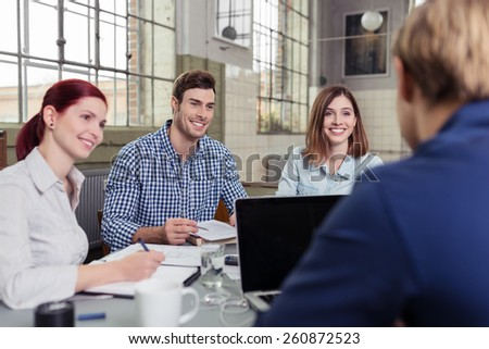 Smiling College Friends Listening to their Friend, Talking About their Lessons, While Taking Down Notes. - stock photo