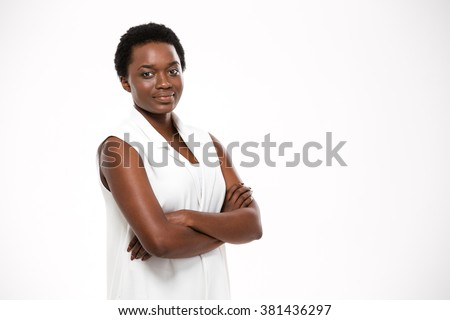 Smiling confident african american young woman standing with arms crossed over white background - stock photo