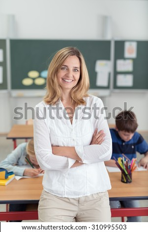 Smiling confident attractive female teacher leaning against a desk in the classroom with folded arms as pupils work in the background - stock photo
