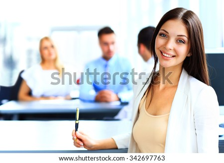 Smiling confident business woman looking at camera with her colleagues in background at office - stock photo