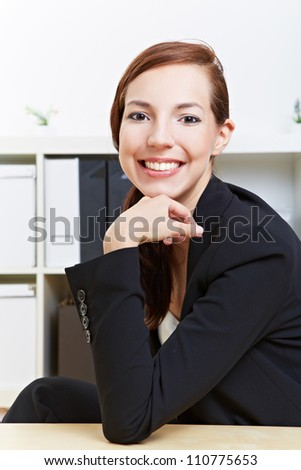 Smiling confident business woman sitting in the office at her desk - stock photo