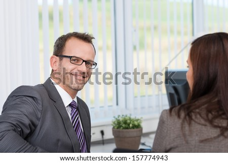 Smiling confident businessman in a discussion with a female colleague in his office - stock photo