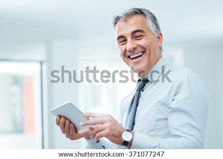 Smiling confident businessman looking at camera and using a digital touch screen tablet - stock photo