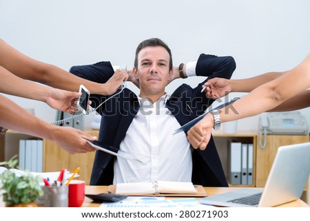 Smiling confident businessman sitting at desk and doing many tasks at once - stock photo