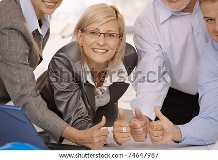 Smiling confident businesswoman giving thumbs up with team in office.? - stock photo