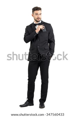 Smiling confident luxurious man in suit putting cellphone in suit pocket looking at camera.  Full body length portrait isolated over white studio background.  - stock photo