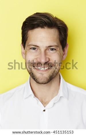 Smiling confident man in yellow studio - stock photo