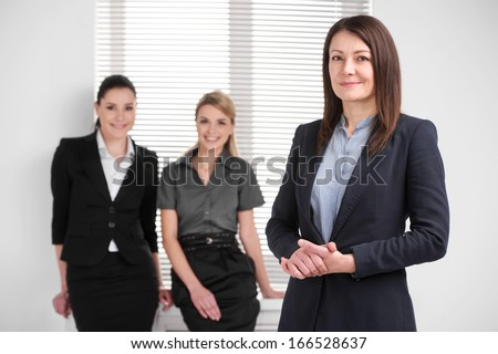 Smiling confident middle aged business woman leading young female business team. Standing together in bright modern office  - stock photo
