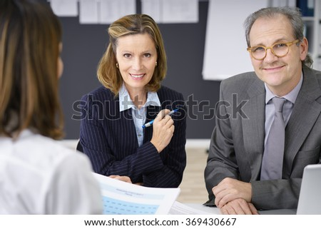 Smiling confident middle-aged couple having a meeting with a female adviser or broker as they plan for their retirement - stock photo