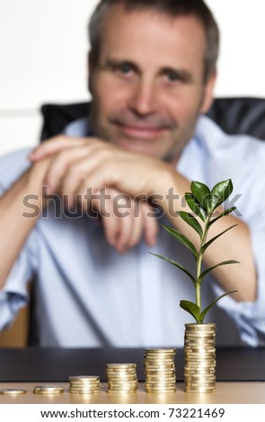 Smiling confident senior business person sitting at desk in front of increasing stacks of coins with growing green plant, looking forward to developing business growth. - stock photo