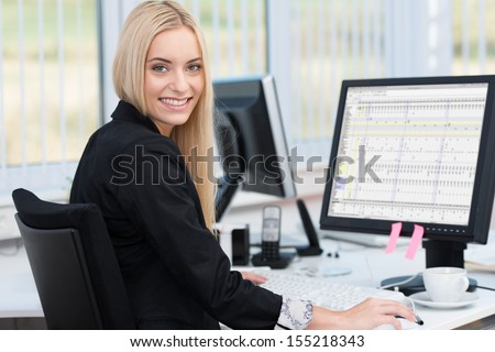 Smiling confident young business woman sitting at her desk in front of a desktop computer turning to smile at the camera - stock photo