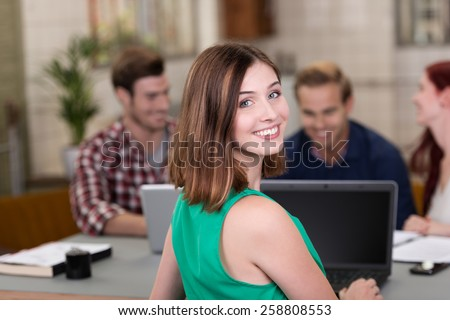 Smiling confident young businesswoman working in a busy office turning to look at the camera - stock photo