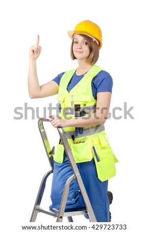 smiling construction female worker in yellow helmet and reflective vest with ladder pointing up on empty copy space for text isolated on white background. proposing service. advertisement gesture - stock photo