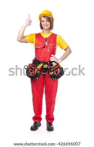 smiling construction female worker in yellow helmet, toolbelt and red workwear showing thumb up gesture isolated on white background. proposing service. advertisement gesture - stock photo