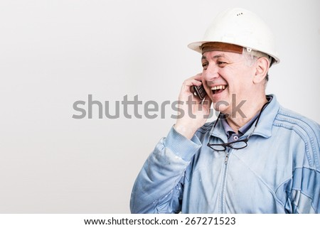 Smiling construction manager talking on the phone - stock photo