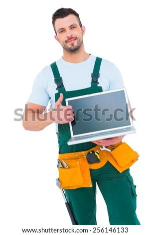 Smiling construction worker holding laptop on white backboard - stock photo