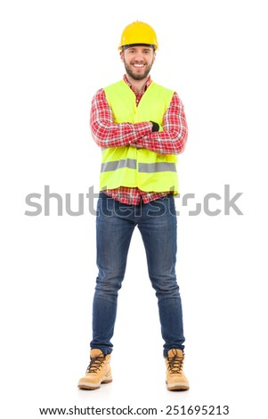 Smiling construction worker in yellow helmet and lime waistcoat posing with arms crossed. Full length studio shot isolated on white. - stock photo