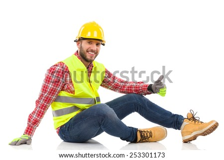 Smiling construction worker in yellow helmet and lime waistcoat sitting relaxed on the floor and showing thumb up. Full length studio shot isolated on white. - stock photo