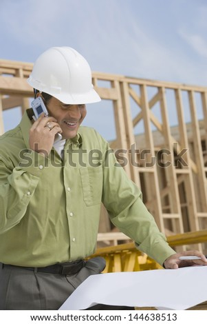 Smiling construction worker with cellphone and blueprints at site - stock photo