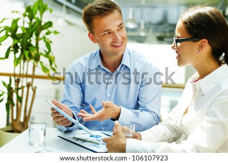 Smiling consultant preferring modern technology to obsolete forms of doing business - stock photo
