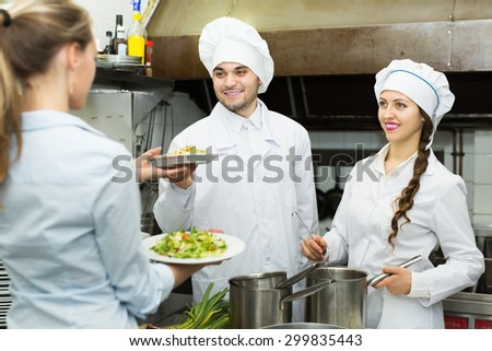 Smiling cook gives to female waitress plates with prepared meal at restaurant kitchen - stock photo