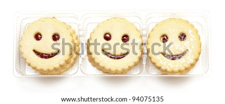 smiling cookies in plastic box isolated on white - stock photo