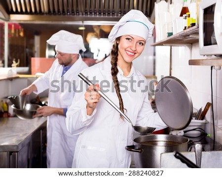 Smiling cooks cooking at professional kitchen in the take-away  restaurant - stock photo