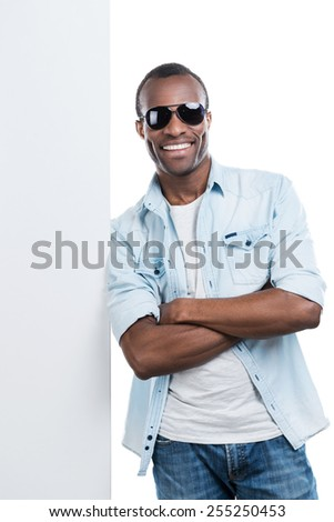 Smiling cool man. Handsome young black man keeping arms crossed and leaning at the copy space while standing against white background  - stock photo