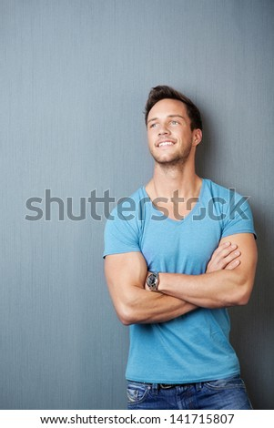 Smiling cool young man standing with arms crossed against gray background - stock photo